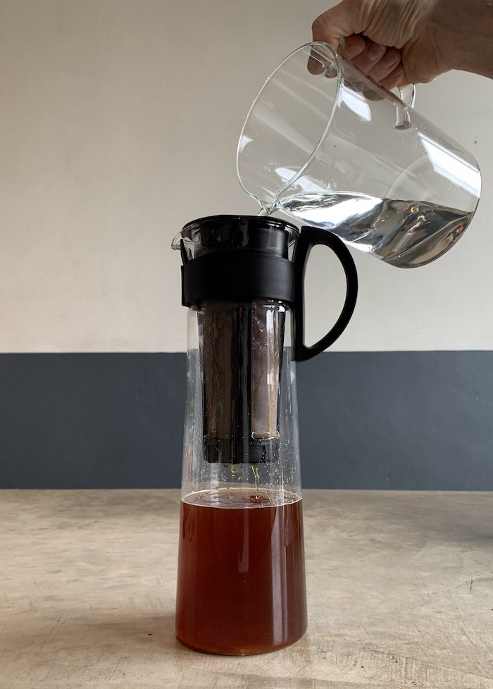 Filling coffee carafe with water to make cold brew.